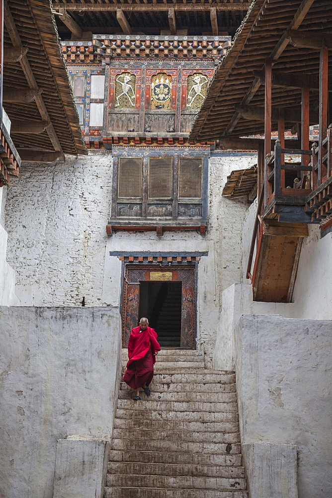 Tibetan monk comes out from Punakha Dzong, the second oldest and most majestic dzong in Bhutan, Asia