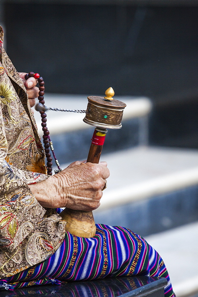 A faithful Buddhist uses the traditional portable roller-book (prayer wheel), Bhutan, Asia