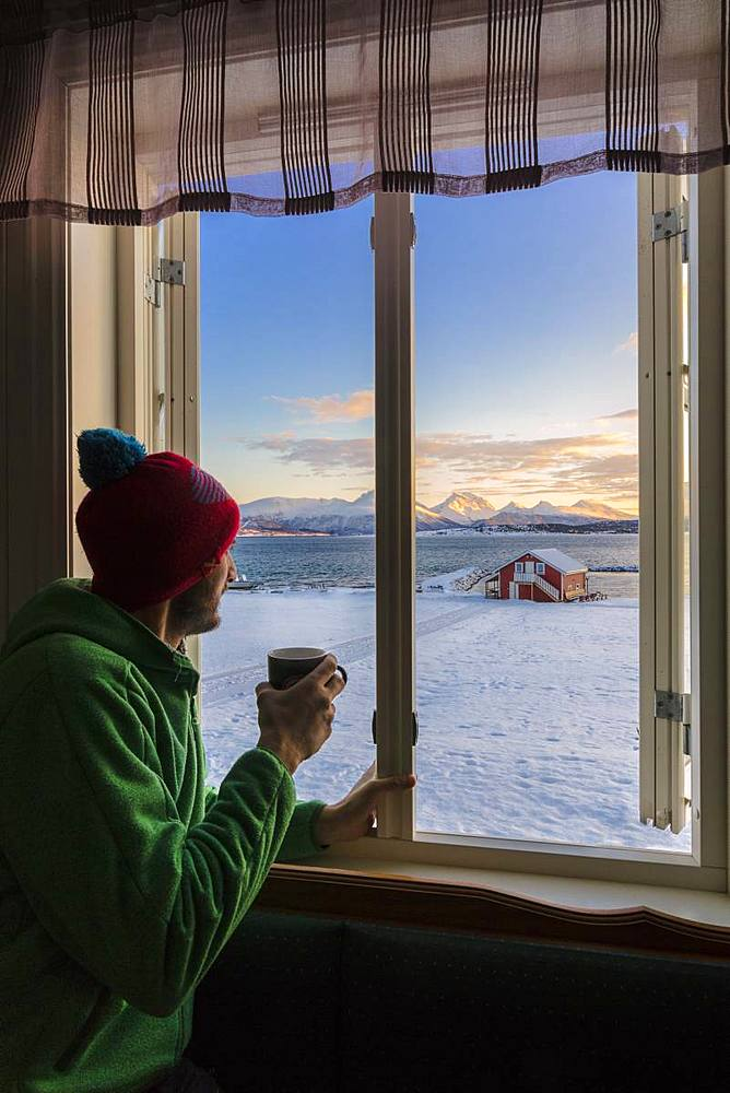 Man looks at the snowy landscape from a window, Troms, Norway, Scandinavia, Europe