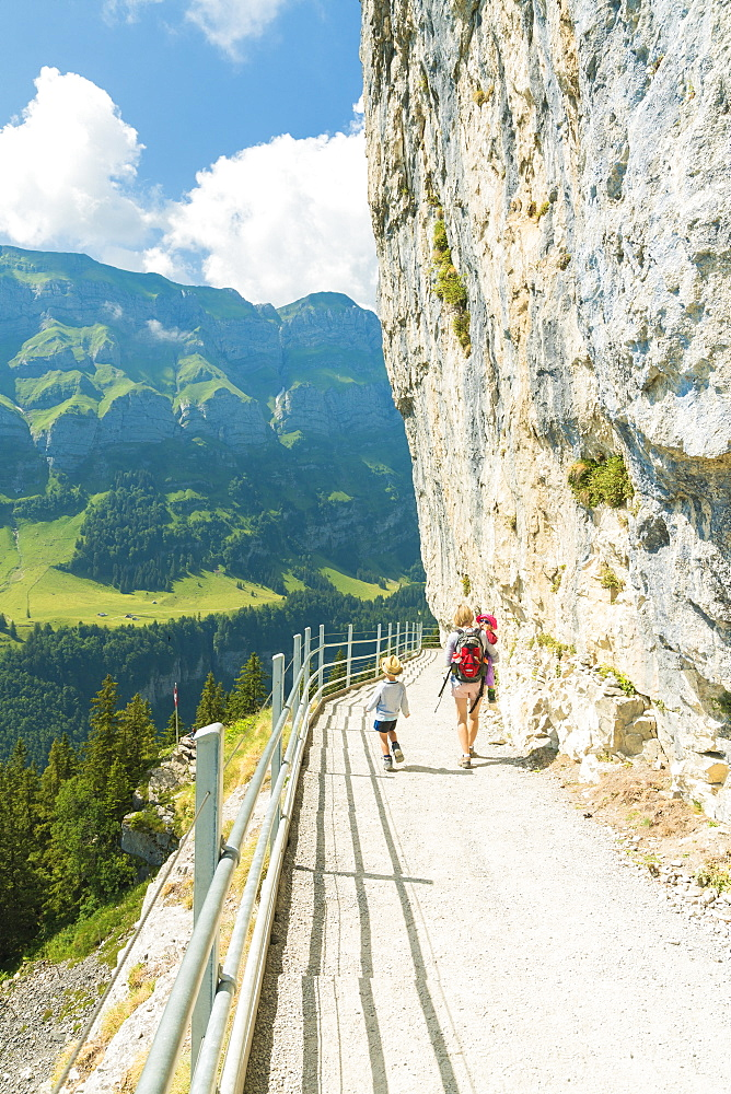 Mother and children on walkway to Aescher-Wildkirchli Gasthaus, Ebenalp, Appenzell Innerrhoden, Switzerland, Europe