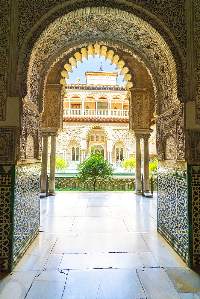 Patio de las Doncellas from interior of a room decorated with mosaic tiled and archways, Real Alcazar, UNESCO World Heritage Site, Seville, Andalusia, Spain, Europe