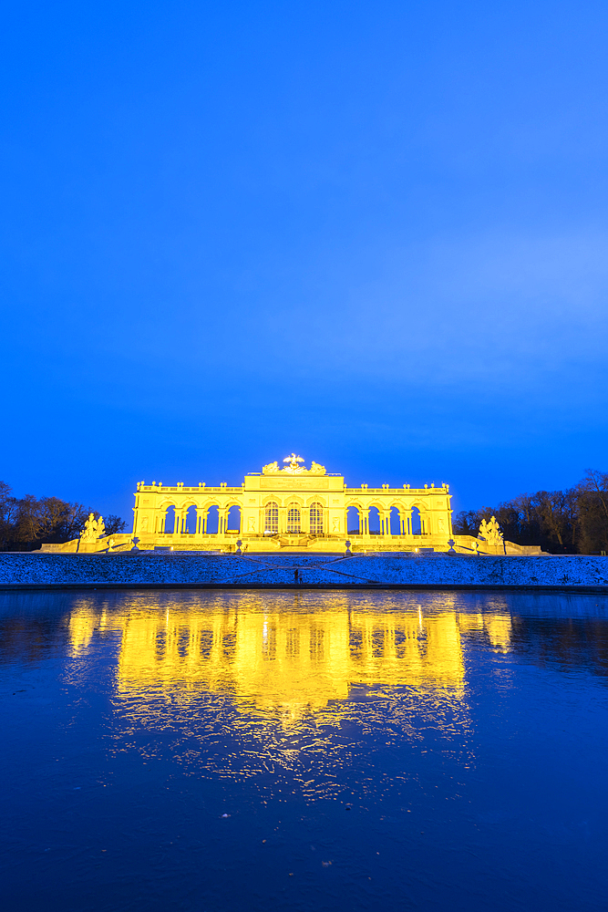 Illuminated Gloriette building mirrored in water at dusk, Schonbrunn Palace, UNESCO World Heritage Site, Vienna, Austria, Europe