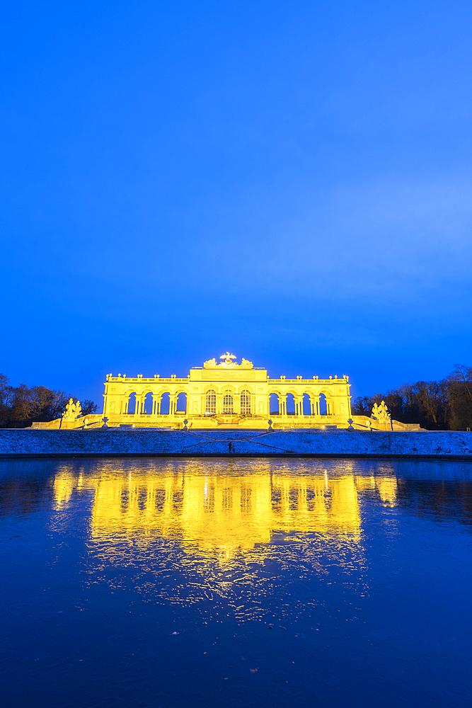 Illuminated Gloriette building mirrored in water at dusk, Schonbrunn Palace, UNESCO World Heritage Site, Vienna, Austria, Europe