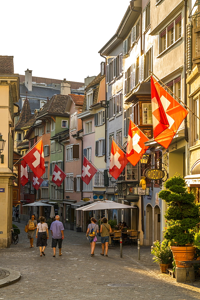 Tourists look at the Swiss flags hanging from buildings in Lindenhof, Zurich, Switzerland, Europe