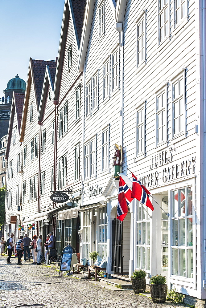 Norwegian flags hanging from white wood buildings and shops, Bryggen, Bergen, Hordaland County, Western Fjords region, Norway, Scandinavia, Europe - 1179-4105
