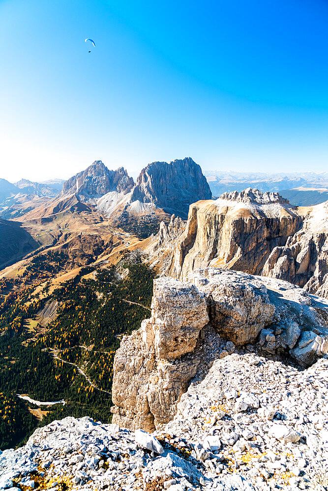 Paragliding over Sassolungo, Sassopiatto and Sella Pass in autumn seen from Sass Pordoi, Dolomites, Trentino, Italy