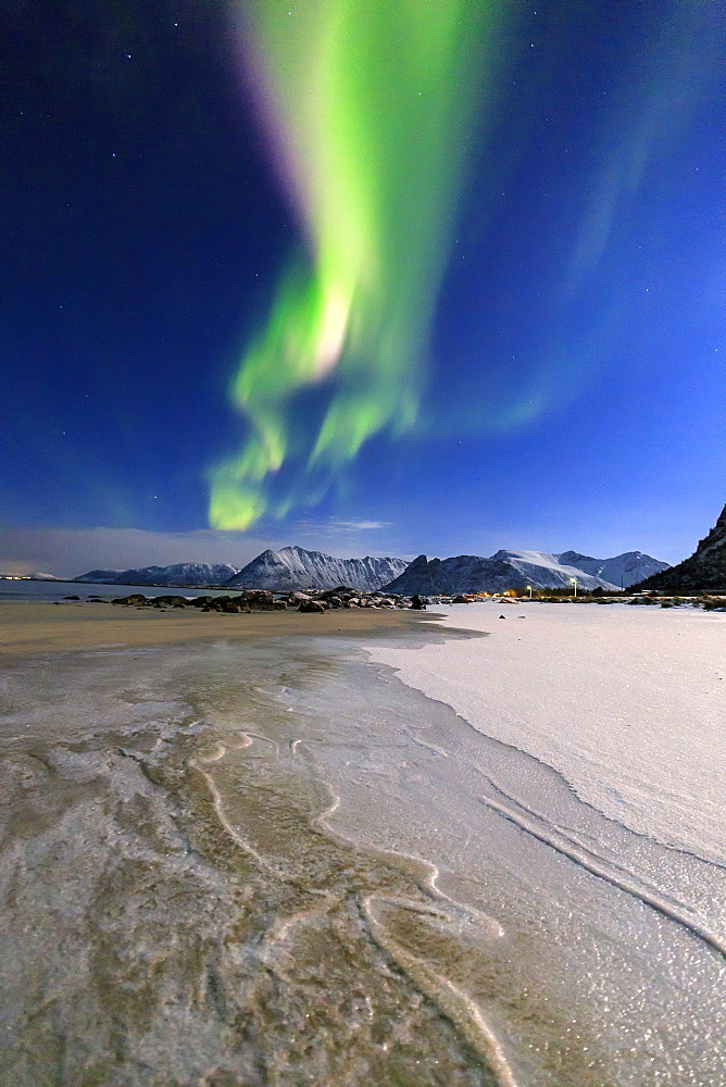 The Northern Lights (aurora borealis) light up the sky and the beach of the cold sea of Gymsoyand (Gimsoy), Lofoten Islands, Arctic, Norway, Scandinavia, Europe