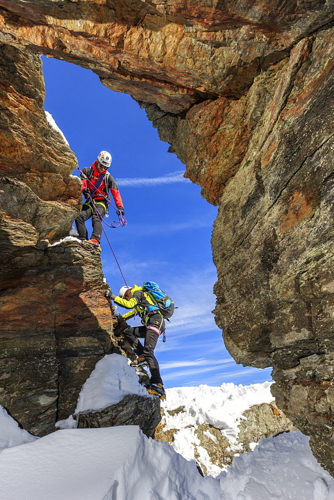 Climbers on the rocks with the snowy peaks of the Alps in the background, Stelvio Pass, Valtellina, Lombardy, Italy, Europe