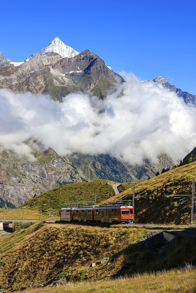 The red Bahn train proceeds with the peak of Dent Herens in the background, Gornergrat, Canton of Valais, Swiss Alps, Switzerland, Europe