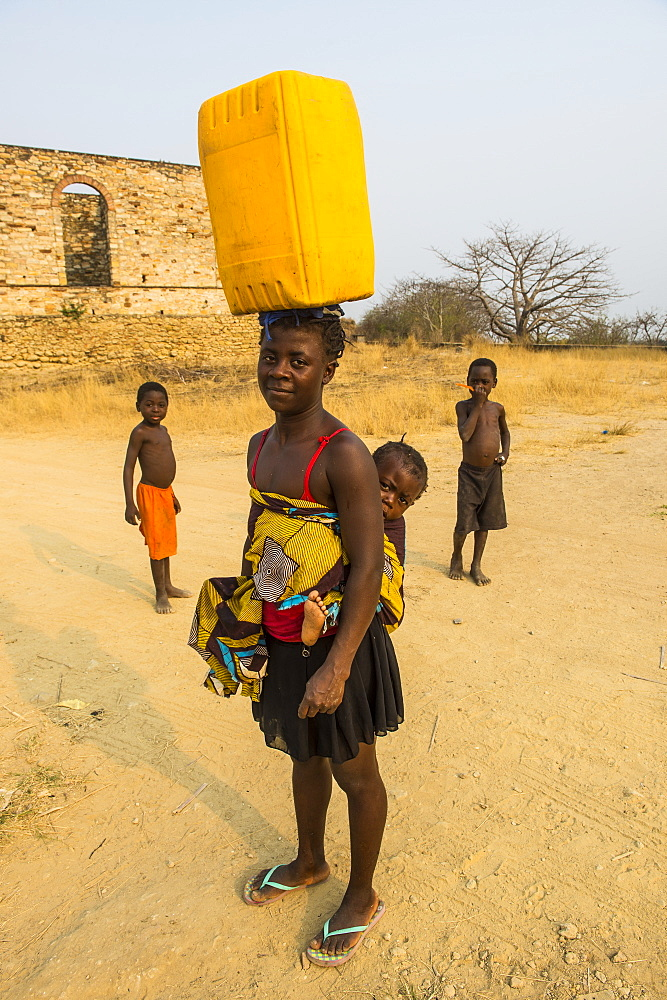 Woman with her baby on the back carrying a water canister on her head, Massangano, Cuanza Norte, Angola - 1184-2000