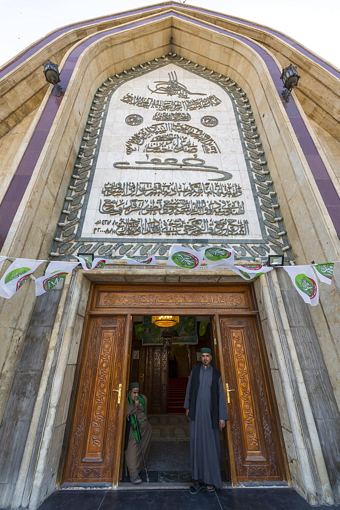 Sufi men standing in the Maruf al-Karkhi sufi mosque, Baghdad, Iraq