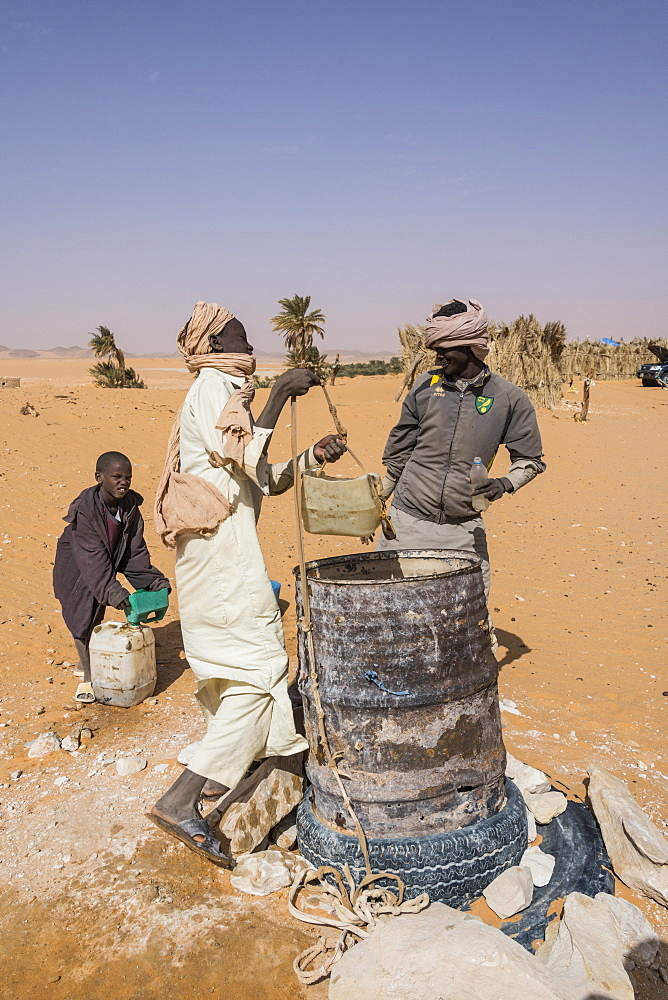 Local boys drawing water from their well in the desert between Ounianga Kebir and Faya, northern Chad, Africa