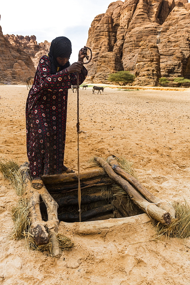 Bedouins pulling water in a beautiful rock amphitheatre in the Ennedi plateau, UNESCO World Heritage Site, Chad, Africa