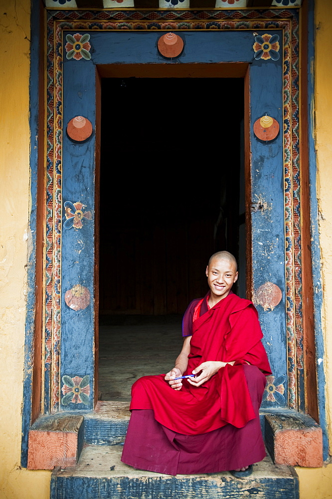 Young monk sitting in an ornate doorway, Punakha, Bhutan, Asia
