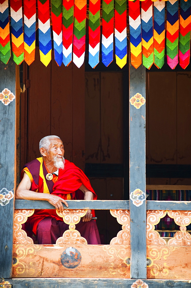Monk watching the dancers at Paro festival, Paro, Bhutan, Asia