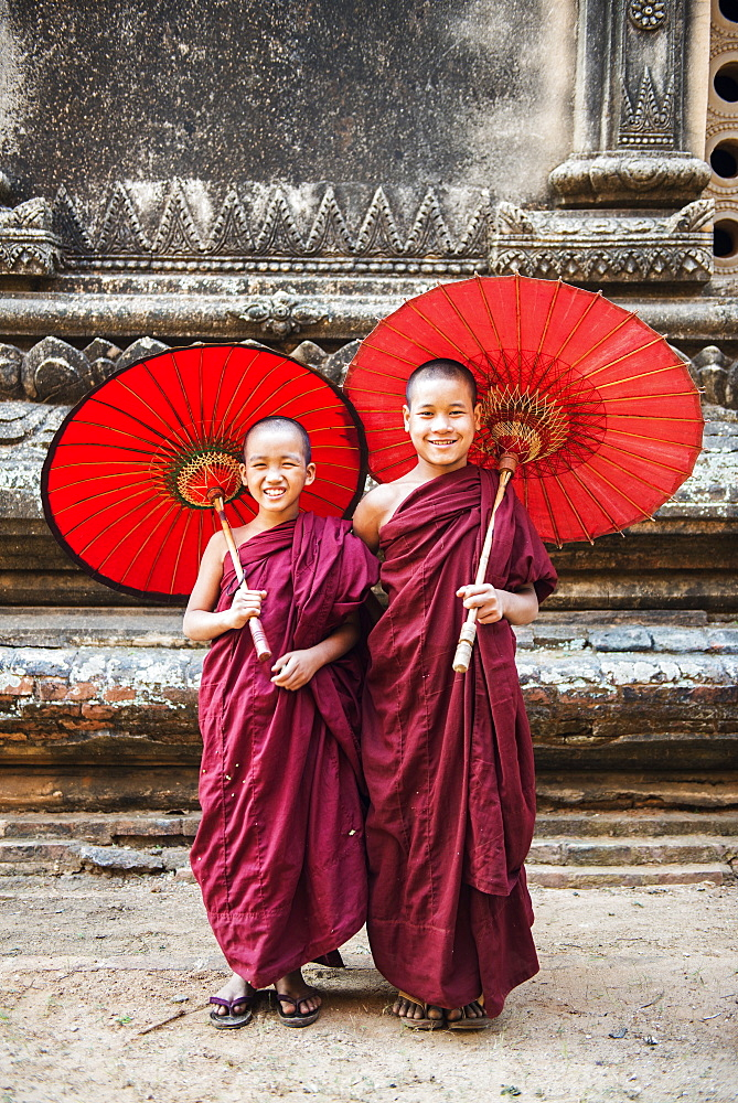 Two young monks and traditional umbrellas, Bagan (Pagan), Myanmar (Burma), Asia