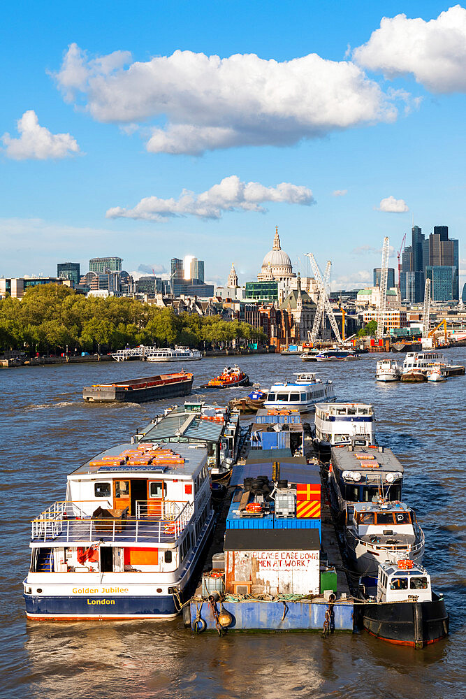 Boats on the river Thames, St Paul's Cathedral and the city from Waterloo bridge