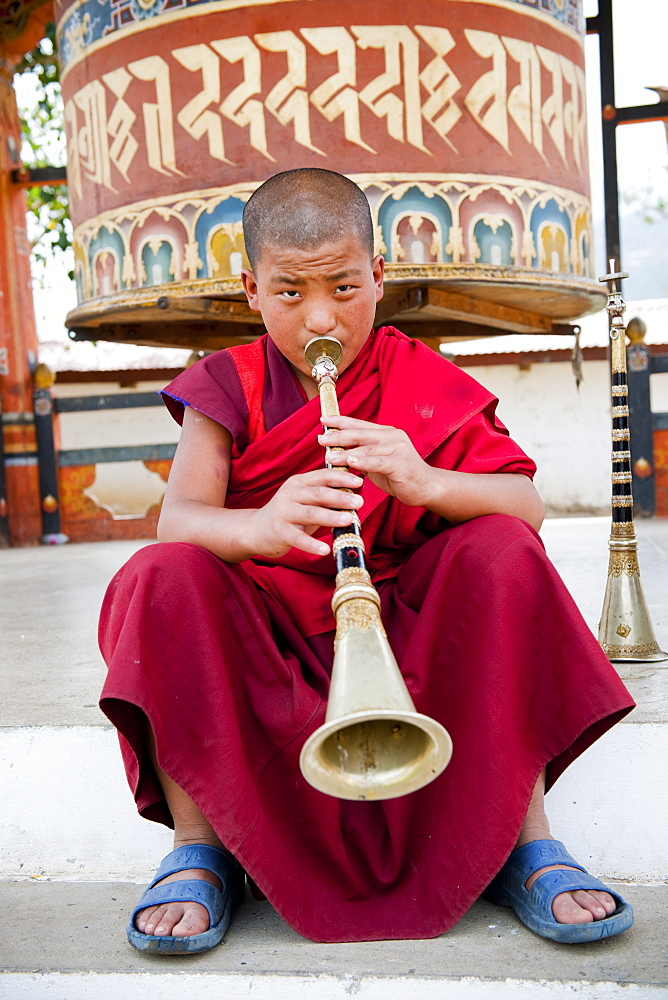 Monk playing lingum trumpet in front of a prayer wheel, Punakha, Bhutan, Asia - 1186-8