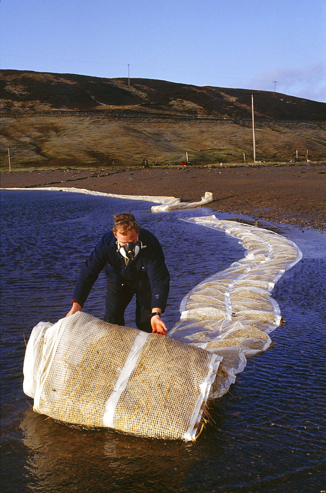 Shetland islands, oil disaster. Deploying oil absorbing straw mats, or frogmats, around salmon farm. On 5th january 1993, the oil tanker the braer ran aground in the shetland islands spilling 85,000 tonnes of light crude oil. However, every single day of the year, roughly one-tenth of the amount of oil abroad the braer is quite deliberately flushed into the worlds seas and oceans by ships cleaning out the tanks and bilges