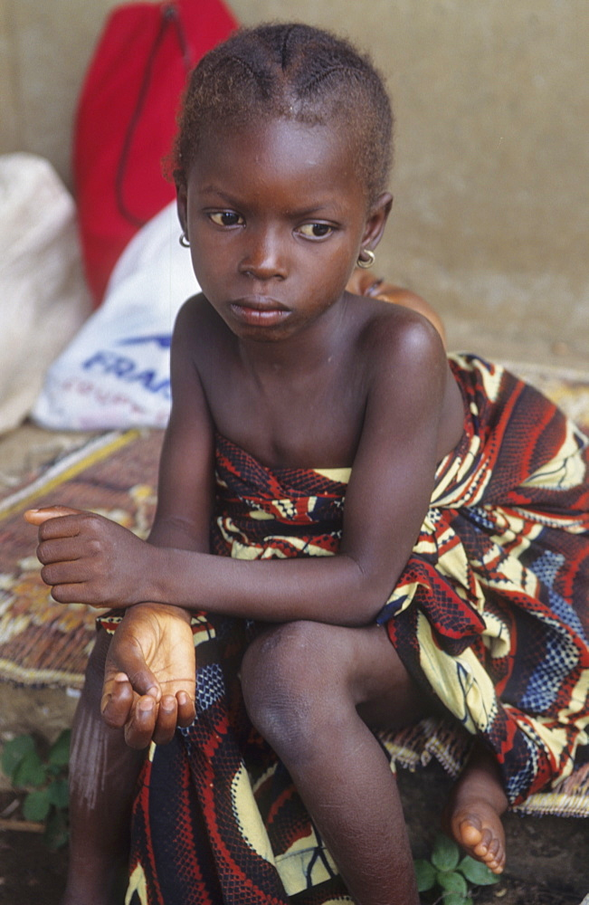 Rural life, ivory coast. Vicinity odienne. Child looking after baby sister