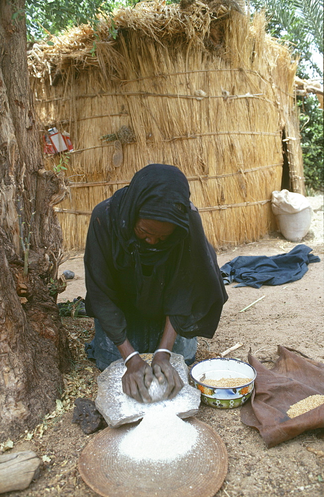 Homelife, niger (west africa). Tahoua village. Elderly woman grinding flour