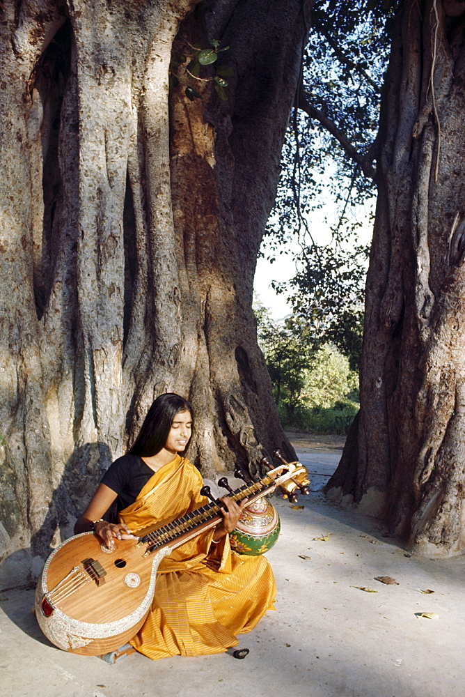 Education,india rishi valley. Rishi valley school. Student playing sitar (classical indian instrument) underneath a banyan tree