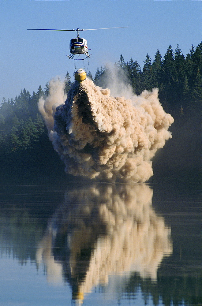 Acid rain, sweden. Vicinity goteborg, lake ovre bergsjon. A helicopter dumps lime into a dying lake to neutralize the acid which is killing it. Sweden spends 100 million kroner (about 10 million pounds) per year on such liming. Britain sends to sweden 10% of the sulphur affecting its forests and lakes