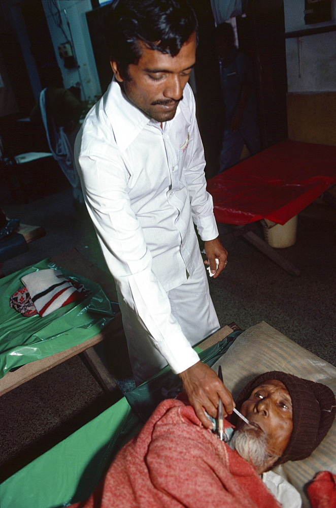 Dacca, bangladesh. An elderly receives treatment in a. population doctor is 9149