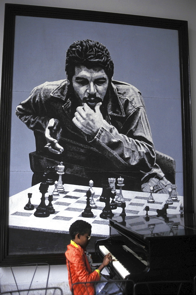 Che' guevara, cuba. A boy playing the piano in front of an iconic picture of the argentinian guerilla leader