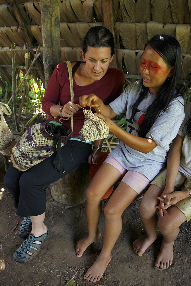 Western tourists on an eco-tourism journey learn local crafts from Huaorani native nation at the Yasuni National Park, Amazon, Ecuador, South America
