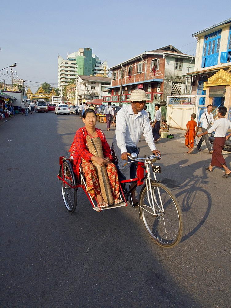Rickshaw carrying woman in the street in Yangon (Rangoon), Myanmar (Burma), Asia