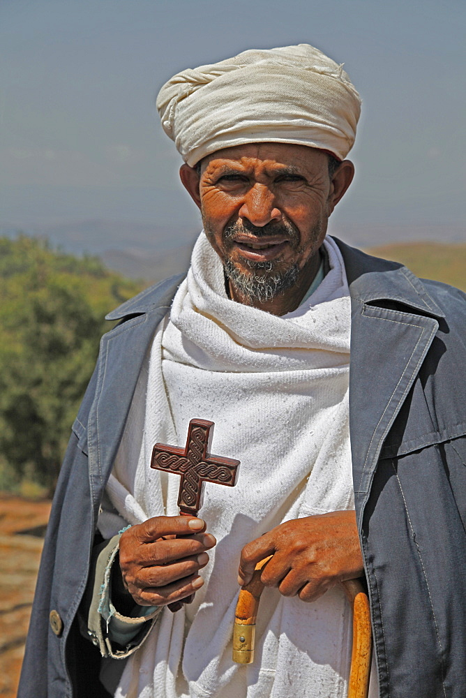 Orthodox priest hold cross at the ancient sunken rock-hewn church of St. George in Lalibela, Ethiopia, Africa - 1188-798