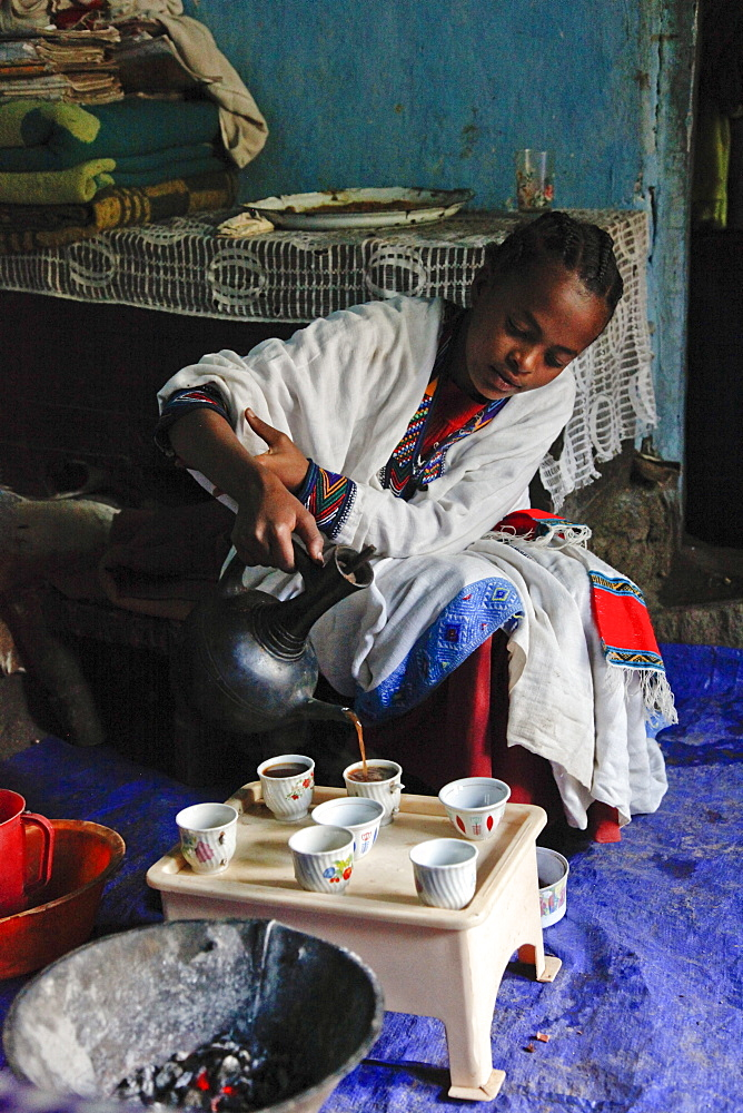 Young woman performing a traditional coffee ceremony in a village in Ethiopia, Africa