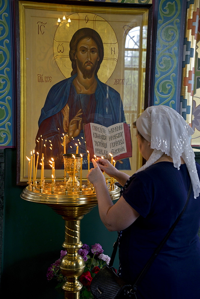 Woman lighting candles at a Russian Orthodox church service in Volgograd, Russia, Europe