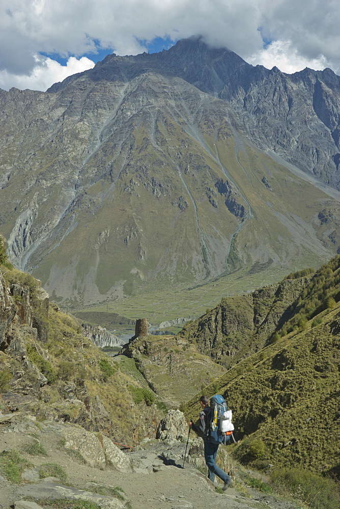 Tourists trekking near the Gergeti Holy Trinity Church by the river Chkheri, under Mount Kazbegi at an elevation of 2170 meters in the Caucasus, Georgia - 1188-925