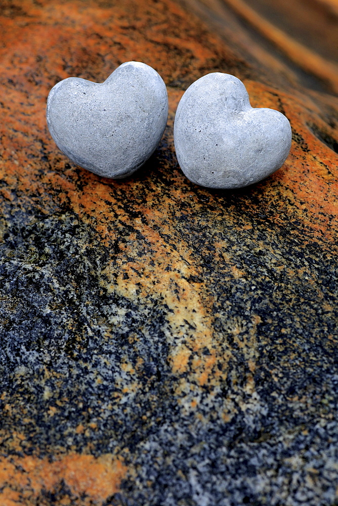 Two heart shaped stones on colourful stones in river bed, valley of verzasca, tessin, switzerland