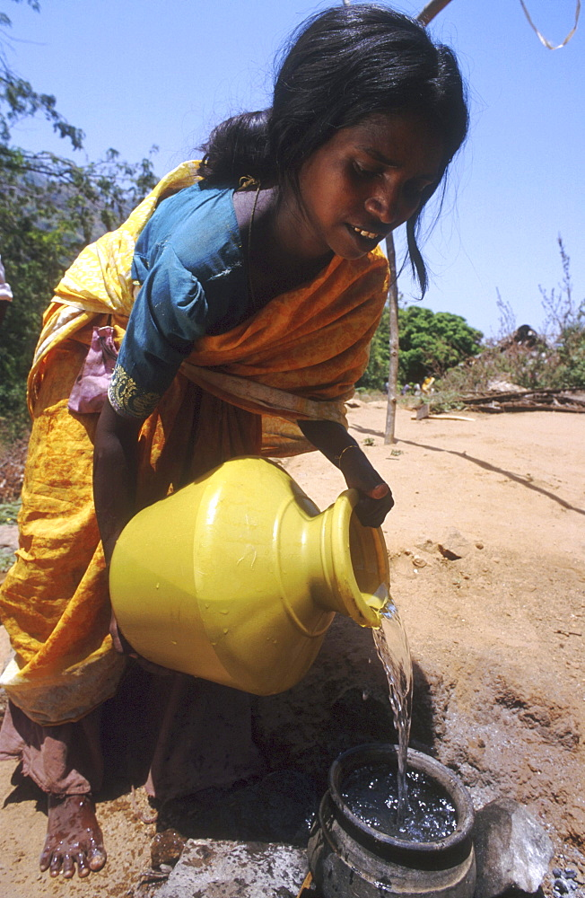 India - water: woman filling cooking pot with water, tamil nadu