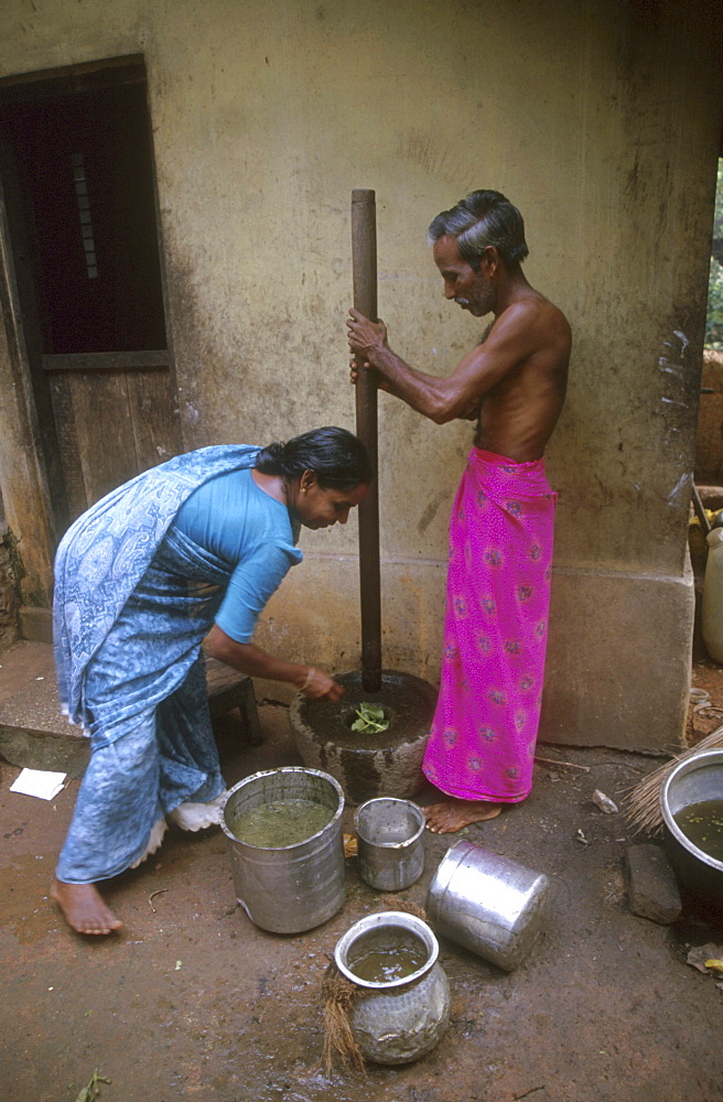 India - food: man and woman grinding herbs, pinkulam village, kerala
