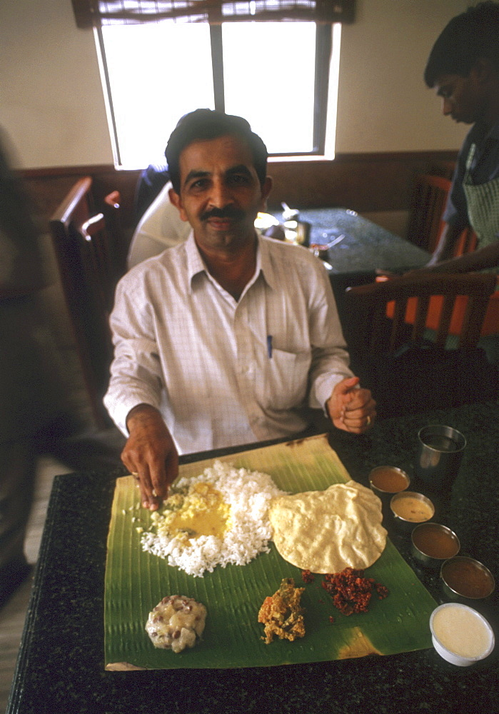 India - food: man eating vegetarian meal from a banana leaf in a restuarant of trivandrum, kerala