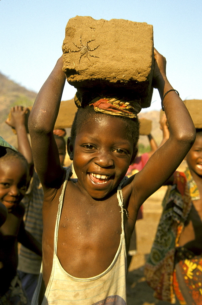 Mozambique boy carrying mud brick, school building project, metangula