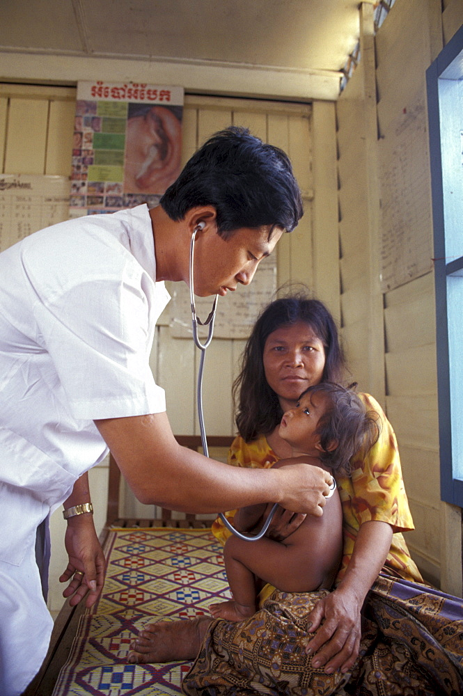Cambodia doctor examining child at floating clinic on tonle sap