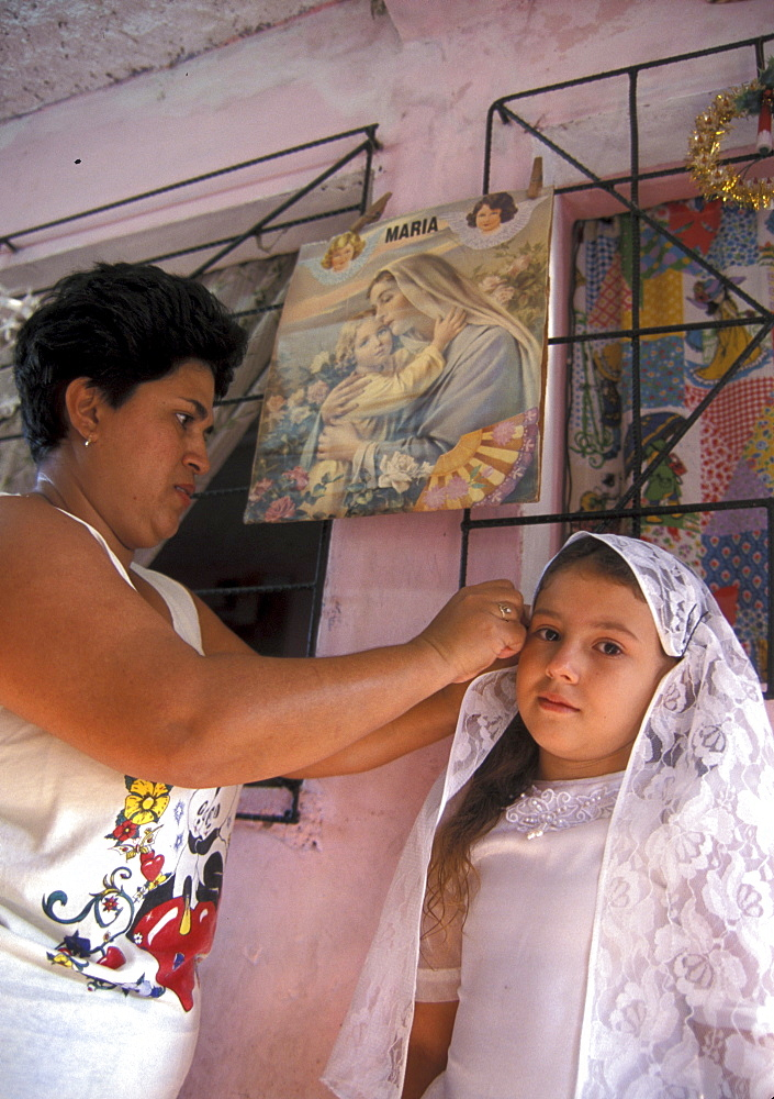 El salvador nother adjusts girls first communion dress, san salvador.