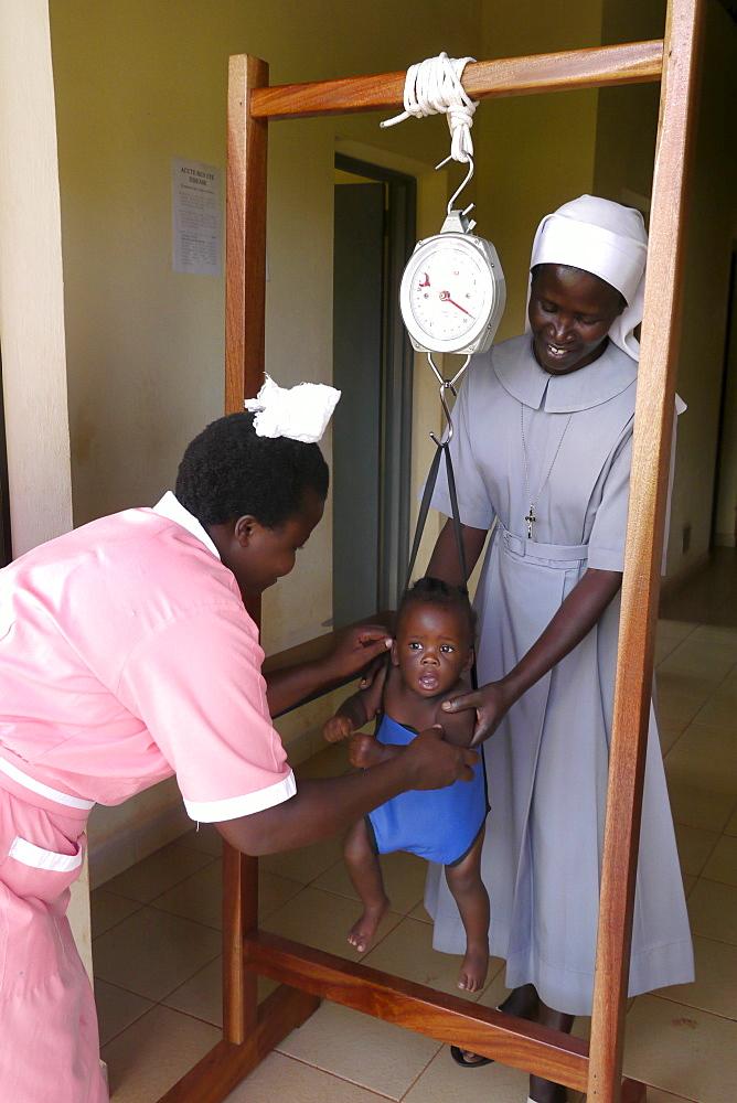 UGANDA St Monica's clinic Gulu. Weighing a baby. PHOTO by Sean Sprague