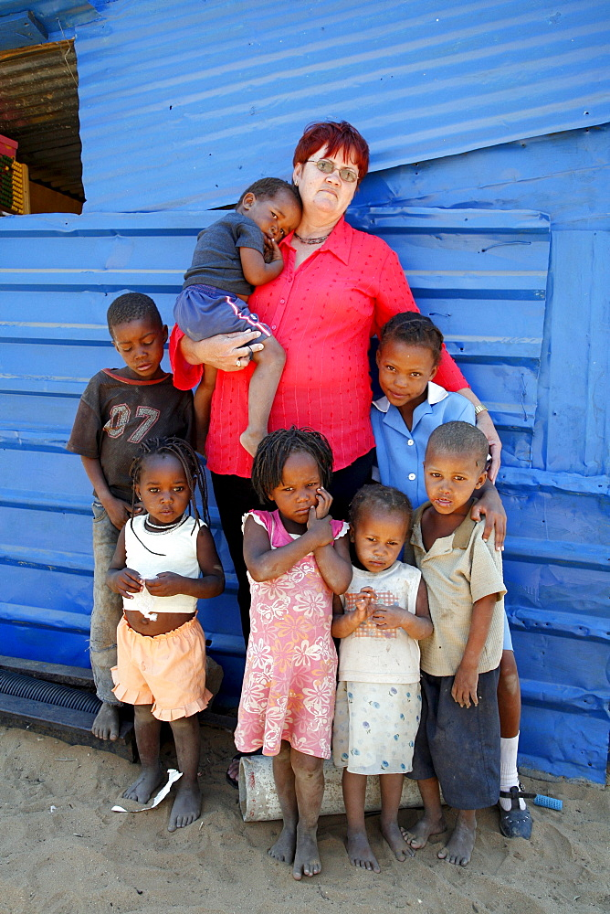 Namibia woman with poor children standing in front of their -school in rehobeth