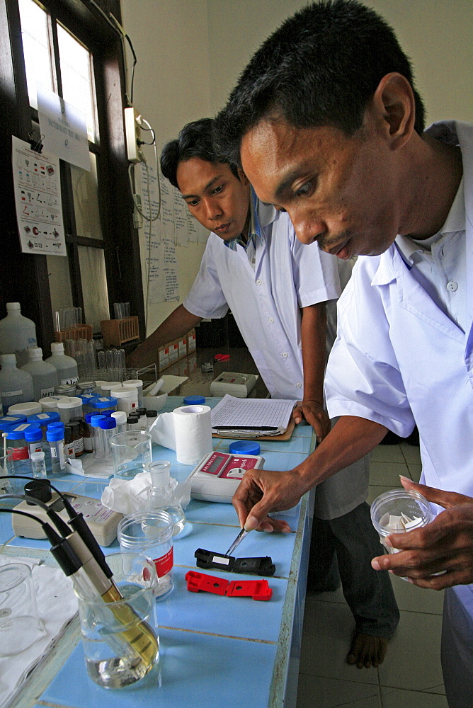 Indonesia laboratory testing drinking water. Photograph taken in meulaboh, aceh province -december 2006, 2 years after tsunami of december 26th 2004 devastated much of coastal region. Taken to illustrate reconstruction work projects of (catholic relief services) of sponsored photo tour. terchnician : every house well gets tested. Unicef originally helped up to support other ngos in area, helps staff salaries provides us with equipment. coordinates activities with local government. water in local wells is quite contaminated, especially with arsenic, as well as nitrates, nitrites, iron, manganese fluoride. water became salinated after tsunami. We test here both water from shallow deep wells