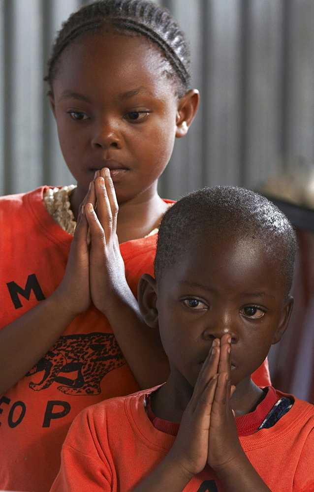 Kenya. Faces of the congregation at catholic mass in mukuru ruben, a slum of nairobi. Children praying