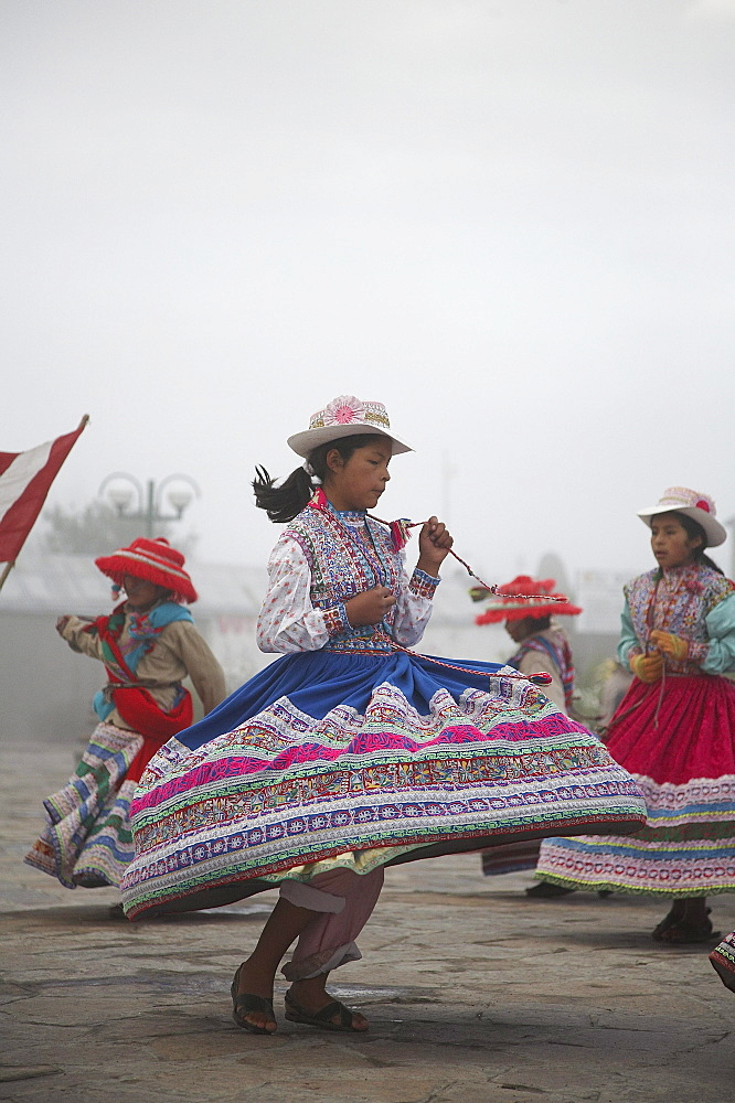 Peru. Children in traditional costume dancing at yanque, colca canyon