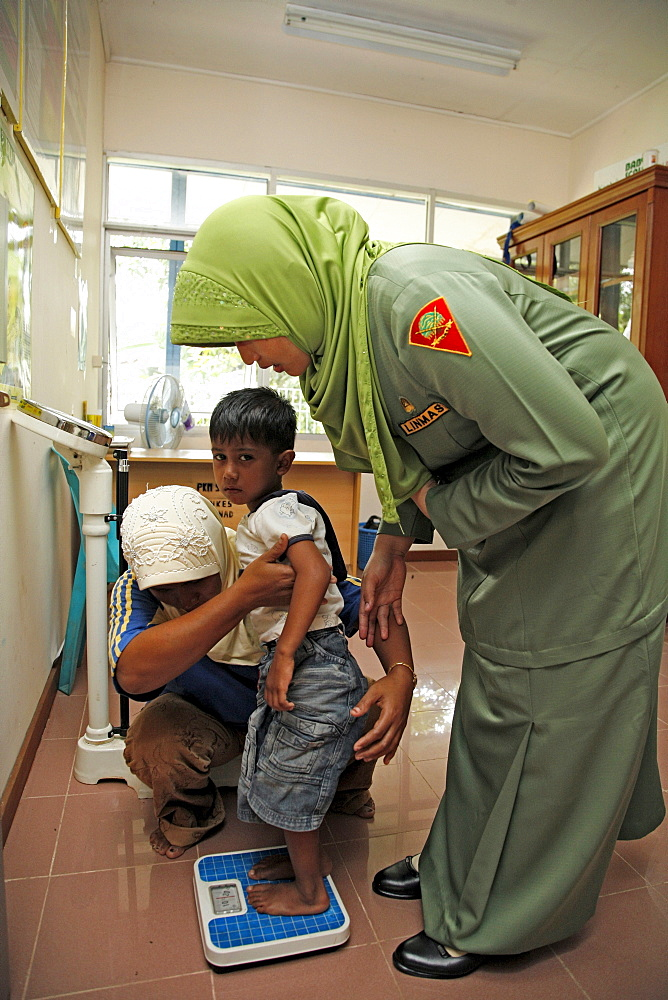 Indonesia government health clinic (pos kesmas) at cot seumereng, desa pucoh leung. weighing a child. meulaboh, aceh