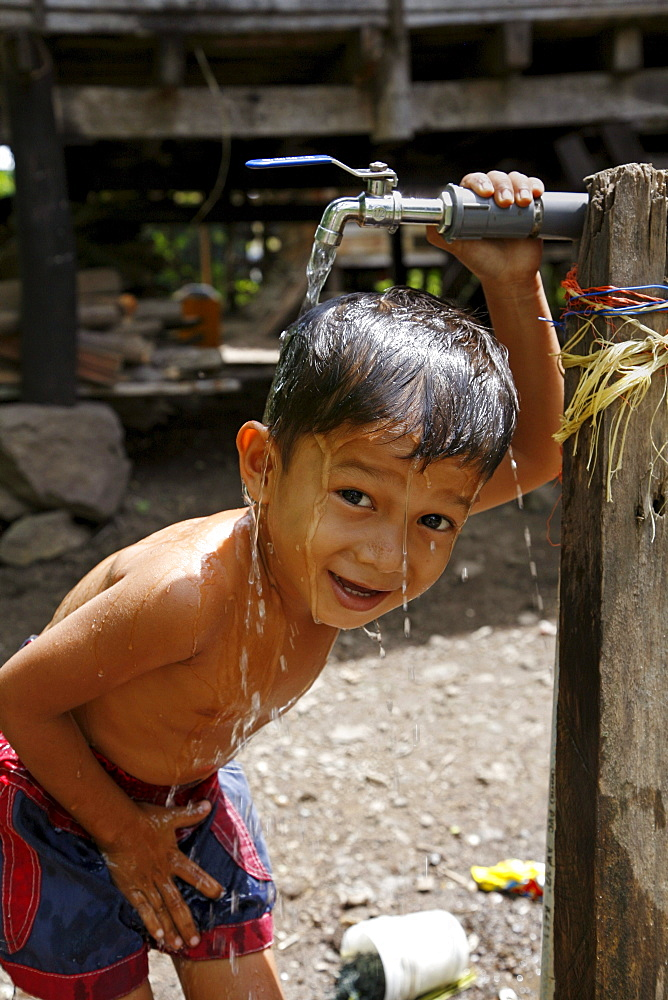 Indonesia boy taking a bath at a crs provided tap in paloh village, pulo aceh, aceh. 2 years after the tsunami