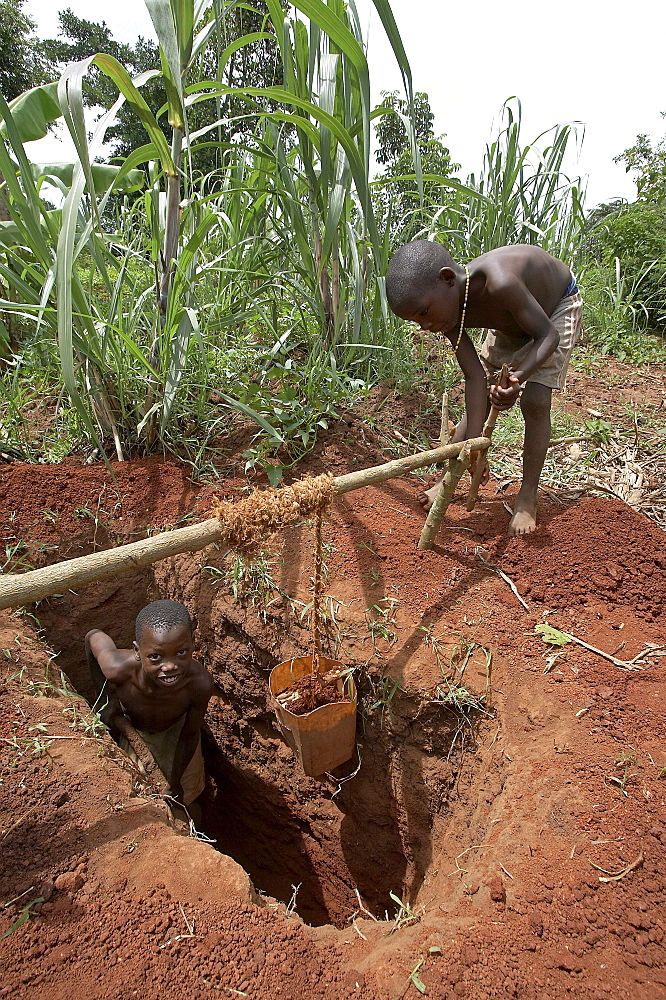 Uganda boys digging a pit latrine, and hauling up the dirt with a winch and small bucket. kayunga district